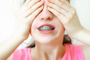 Girl with braces covering her eyes